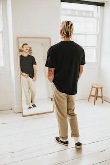 Modieuze man die zichzelf in de spiegel bekijkt