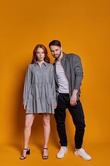 Modieuze man en vrouw in feestkleding poseren samen geïsoleerd op oranje muur.