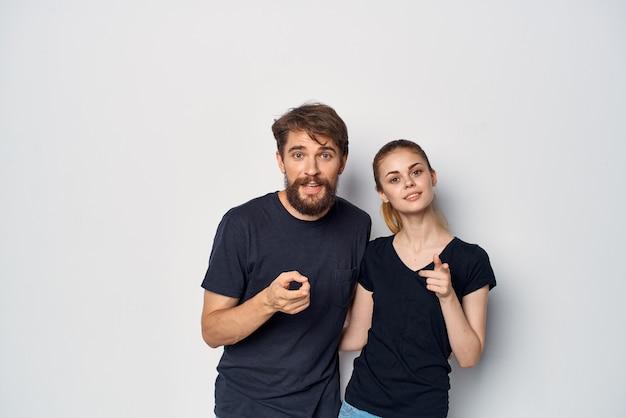 Modieuze man en vrouw in zwarte tshirt zonnebril poseren geïsoleerde achtergrond