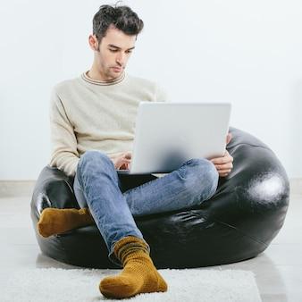 Modieuze man in de winter gebreide kleding met laptop