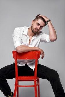 Modieuze man in een wit overhemd zit op een stoel op een grijze muur