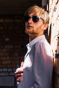 Modieuze man in zonnebril voor een bakstenen muur
