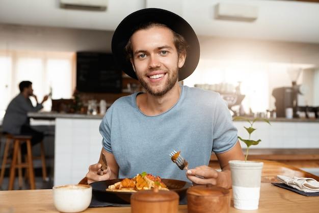 Modieuze man met baard honger stillen tijdens een diner alleen in modern restaurant op zonnige dag, maaltijd eten met mes en vork