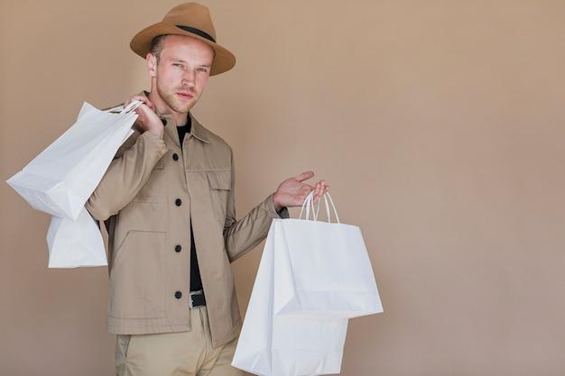 Modieuze man met boodschappentassen op zoek naar de camera