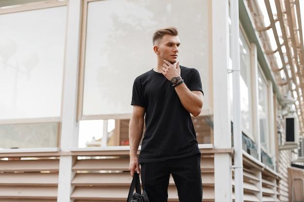 Modieuze man met kapsel in zwart mockup-shirt op straat in de buurt van een houten gebouw