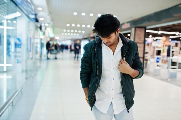 Modieuze man op wit overhemd en jas gesteld op winkelcentrum
