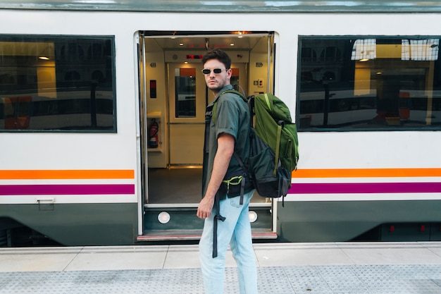 Modieuze mannelijke toerist die oogglazen dragen en rugzak dragen die zich voor spoorwegtrein bevinden