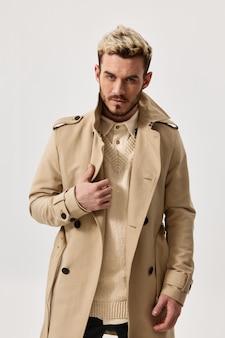 Modieuze mannen in een lichte jas en trui op een geïsoleerd kapselmodel als achtergrond
