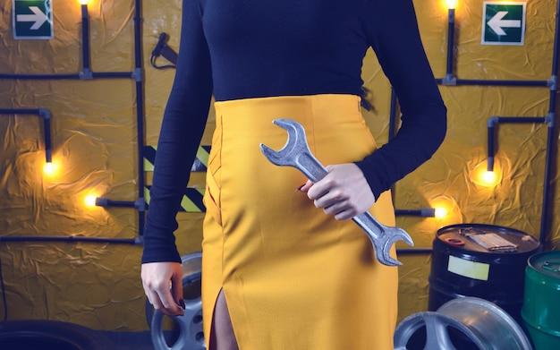 Modieuze mechanische vrouw in trendy kleding houdt een sleutel
