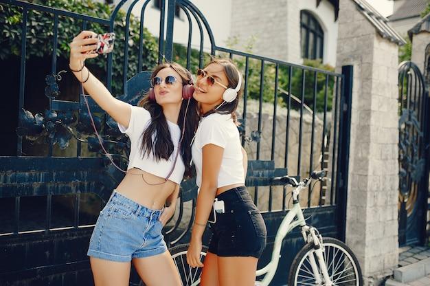 Modieuze meisjes die in een de zomerpark lopen