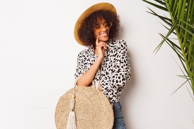 Modieuze mix race meisje in trendy blouse en strooien hoed staande over witte muur. perfecte witte glimlach. shopping stemming.