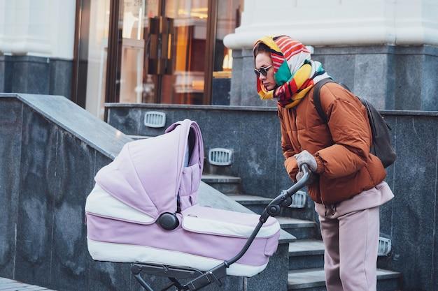 Modieuze moderne moeder met een kinderwagen op een wandeling in de stad, herfst. mam rijdt een kinderwagen door de straten, close-up.