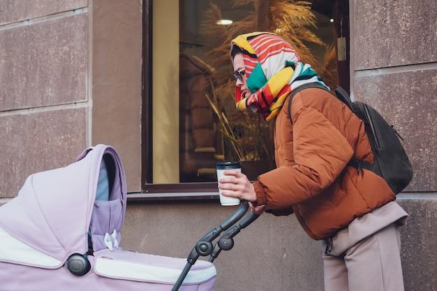 Modieuze moderne moeder met een kinderwagen tijdens een wandeling in de stad, herfst