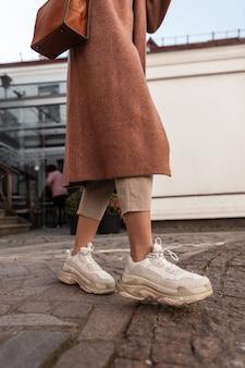 Modieuze moderne vrouw in lange elegante jas met bruine leren handtas in stijlvolle sneakers staat op stenen weg. close-up van vrouwelijke benen in trendy kleding en jeugd mode schoenen. casual lente-outfit.