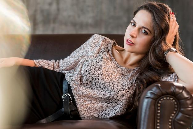 Modieuze modieuze jonge vrouw die op comfortabele bank ligt die camera bekijkt