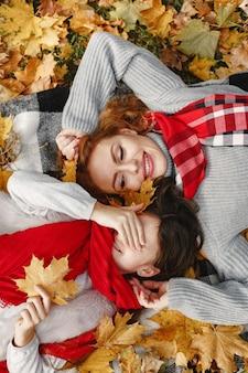 Modieuze moeder met dochter. gele herfst. vrouw in een rode sjaal.