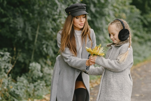 Modieuze moeder met dochter. mensen lopen naar buiten. vrouw in een grijze jas.