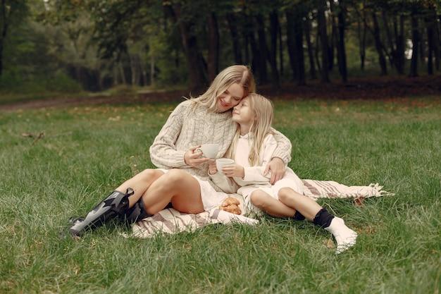 Modieuze moeder met dochter. mensen zitten op een gras