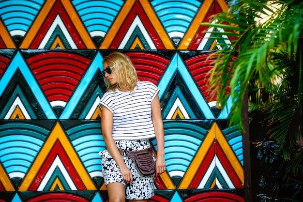 Modieuze mooie blonde in donkere glazen, staande tegen een lichte muur met geometrische patronen. het concept van recreatie, toerisme en reizen. zomervakantie