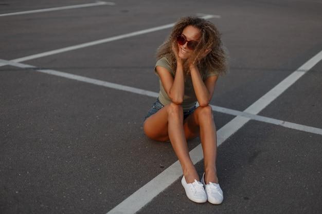 Modieuze mooie gelukkige jonge krullende modelvrouw met glimlach die met zonnebril in modieuze jeanskleren op het asfalt zitten