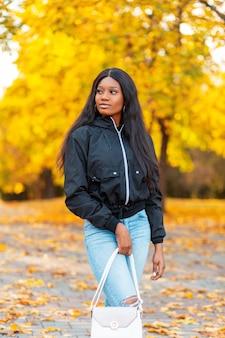 Modieuze mooie jonge afro-amerikaanse vrouw in stijlvolle casual zwarte jas met spijkerbroek en spijkerbroek met een handtas wandelingen in een herfstpark met kleurrijke gouden bladeren