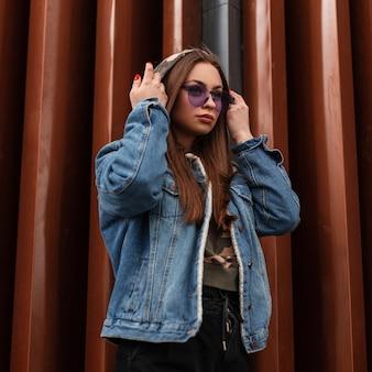 Modieuze mooie jonge hipster vrouw zet een capuchon op. aantrekkelijk meisjesmodel in stijlvol spijkerjasje met glamoureuze paarse bril die zich voordeed in de buurt van moderne metalen wand. amerikaanse jeugd moderne mode.