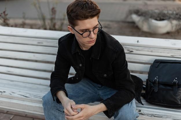 Modieuze mooie jonge man in stijlvolle bril in trendy casual jeans kleding met lederen rugzak zittend op houten vintage bankje op straat in de stad. knappe aardige vent mannequin buitenshuis.