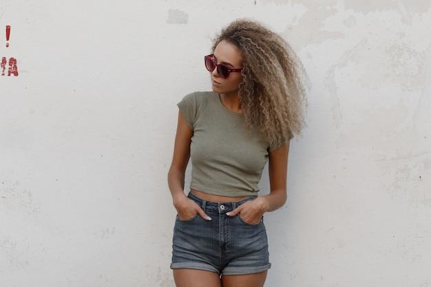 Modieuze mooie jonge sexy model vrouw met krullend haar in een t-shirt en denim stijlvolle korte broek staat in de buurt van een witte muur op straat