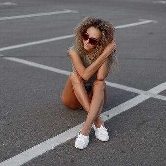 Modieuze mooie jonge stijlvolle hipster vrouw met zonnebril in jeans korte broek, trendy t-shirt en witte schoenen zit op het asfalt