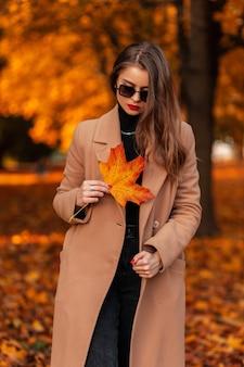 Modieuze mooie jonge vrouw in stijlvolle vintage beige jas en trui met geel gekleurd herfstblad loopt in het park