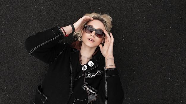 Modieuze mooie jonge vrouw in stijlvolle zwarte blazer in trendy zonnebril rust op asfalt op straat op zomerdag. mooi modern tienermeisje ontspant buitenshuis