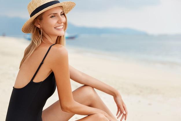 Modieuze mooie jonge vrouw in zwarte zwembroek zit op het strand, bewondert het azuurblauwe uitzicht op de oceaan en de wolkenloze lucht, recreëert op het zandstrand, zonnebaadt en voelt zich ontspannen. vrouwelijke toerist verkent nieuwe plekken