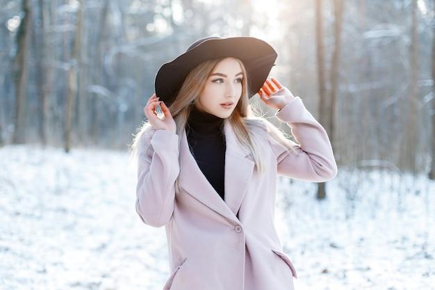 Modieuze mooie jonge vrouw met blond haar in een vintage chique zwarte hoed in een roze elegante jas poseren in een winterpark. charmante stijlvolle meisje rusten in de natuur.
