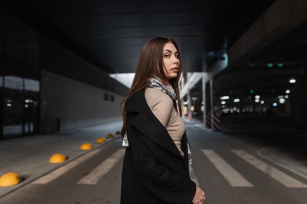 Modieuze mooie jonge vrouw met bruin haar in zwarte modieuze jas in hemd staat op de weg in de straat. vrij moderne luxe meisje mannequin loopt buiten. trendy dame.