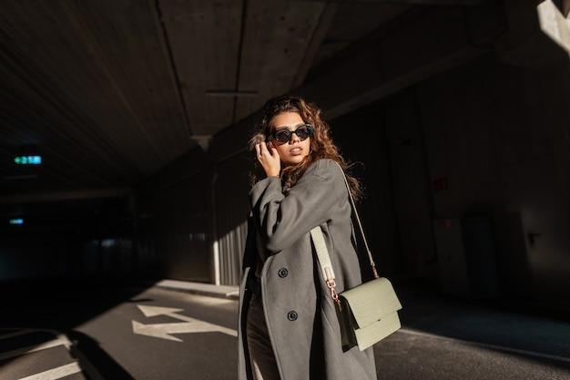 Modieuze mooie jonge vrouw met krullend haar en stijlvolle zonnebril in een modieuze lange jas met een vintage tas wandelingen in de stad. stedelijke vrouwelijke stijl en schoonheid. zonlicht en schaduw