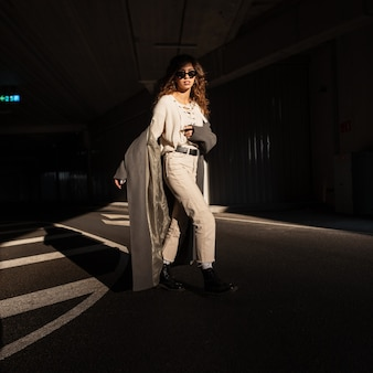 Modieuze mooie jonge vrouw met krullend haar met zonnebril in een stijlvolle jas met een wollen gebreide blouse en broek loopt op straat in het zonlicht