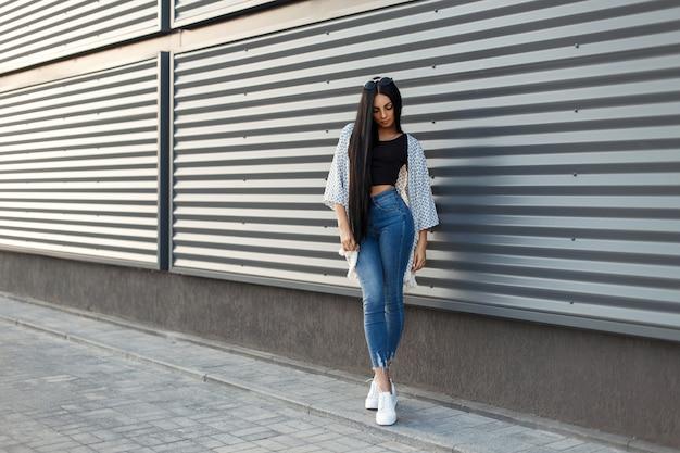 Modieuze mooie jonge vrouw met lang zwart haar in een stijlvolle witte cape