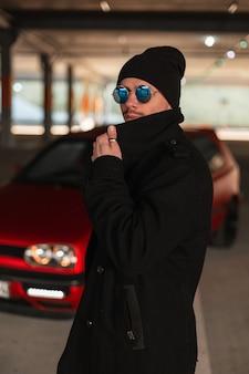 Modieuze mooie jonge zakenvrouw met bril in een witte hoed en een zwarte jas op straat. stijlvol mooi meisje in modieuze zomerkleren