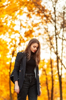 Modieuze mooie stijlvolle vrouw in een zwarte mode pak look met blazer trui, jeans en een rugzak wandelingen in een herfst park met geel gebladerte bij zonsondergang