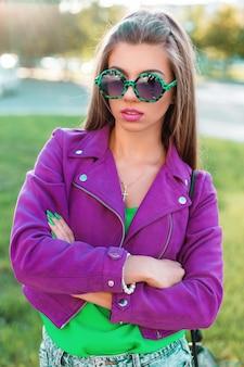 Modieuze mooie vrouw in een roze jasje met zonnebril poseren in het park.