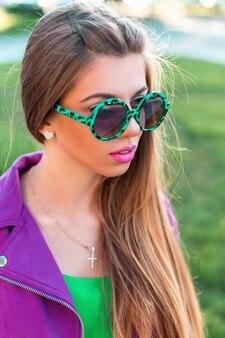 Modieuze mooie vrouw in een roze jasje met zonnebril