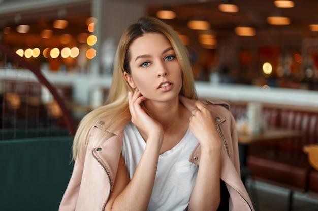 Modieuze mooie vrouw in een stijlvolle roze jas poseren in een café