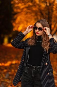 Modieuze mooie vrouw in elegant zwart pak met blazer zet stijlvolle zonnebril buiten recht met oranje gebladerte bij zonsondergang