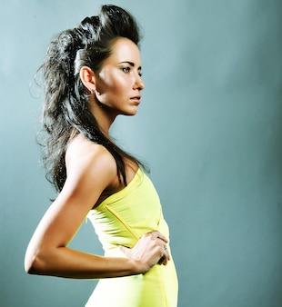 Modieuze mooie vrouw in gele jurk