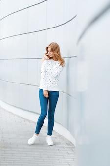 Modieuze mooie vrouw op de achtergrond van moderne lichte muur