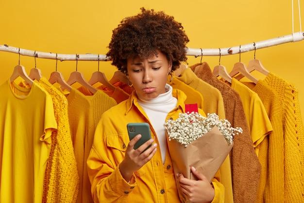 Modieuze ontevreden vrouwelijke klant kijkt boos, gefocust op smartphone, houdt boeket vast, poseert tegen kleding in één toon hangend aan rails, kiest outfit om te dragen