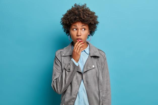 Modieuze opgewonden jonge krullende vrouw kijkt met geschokte doordachte uitdrukking, houdt hand op mond, gefocust opzij, draagt grijze stijlvolle jas,