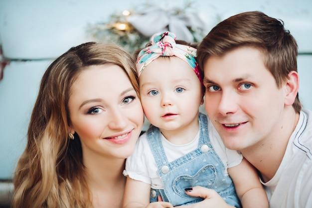 Modieuze ouders houden op handen kleine schattige dochter, staande in de buurt van blauwe retro auto.