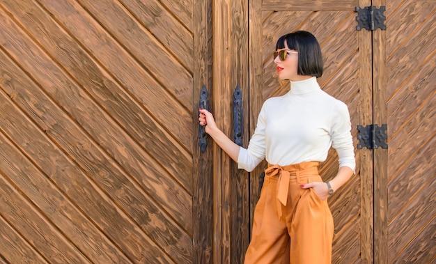 Modieuze outfit slanke lange dame. mode en stijl concept. vrouw lopen in elegante outfit. vrouw modieuze brunette staan buiten houten achtergrond. meisje met make-up poseren in modieuze kleding.