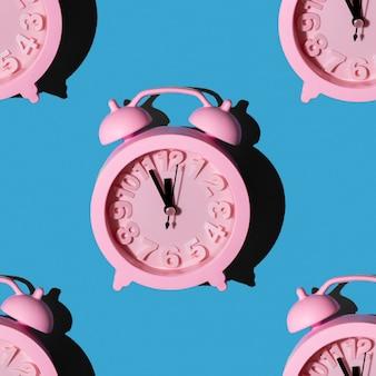 Modieuze patronen met roze klokken op blauwe achtergrond herhalend behang met minimalistische naadloze lay-out. nieuwjaar om middernacht concept